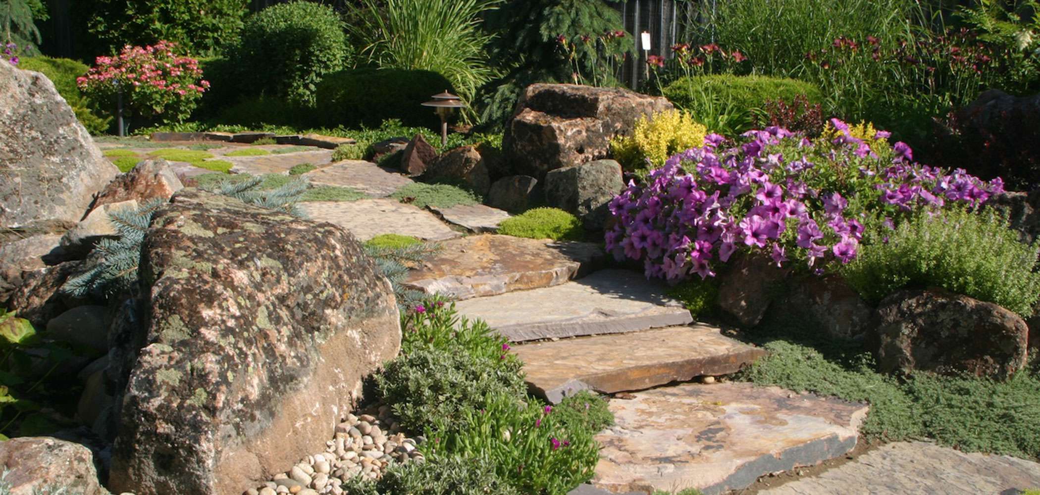 Natural flagstone steps and landscape boulders design.