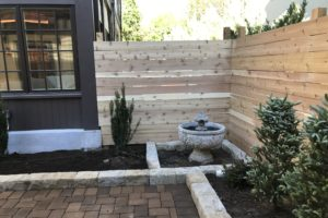 Custom back area of a home with paver patio, stone planters, and cedar wood fence.