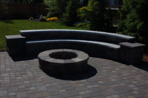 A custom paver patio with rised fire pit and seating area.