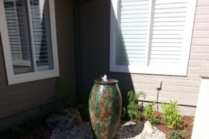 A outdoor water feature decorating the side of a home.