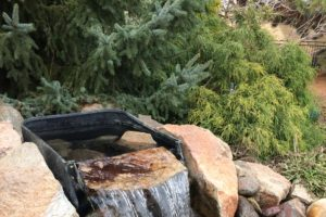 A clean running water feature maintained by FarWest Landscape.